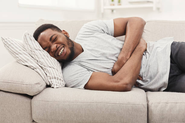 handsome young african-american man suffering from stomachache - china drug foto e immagini stock