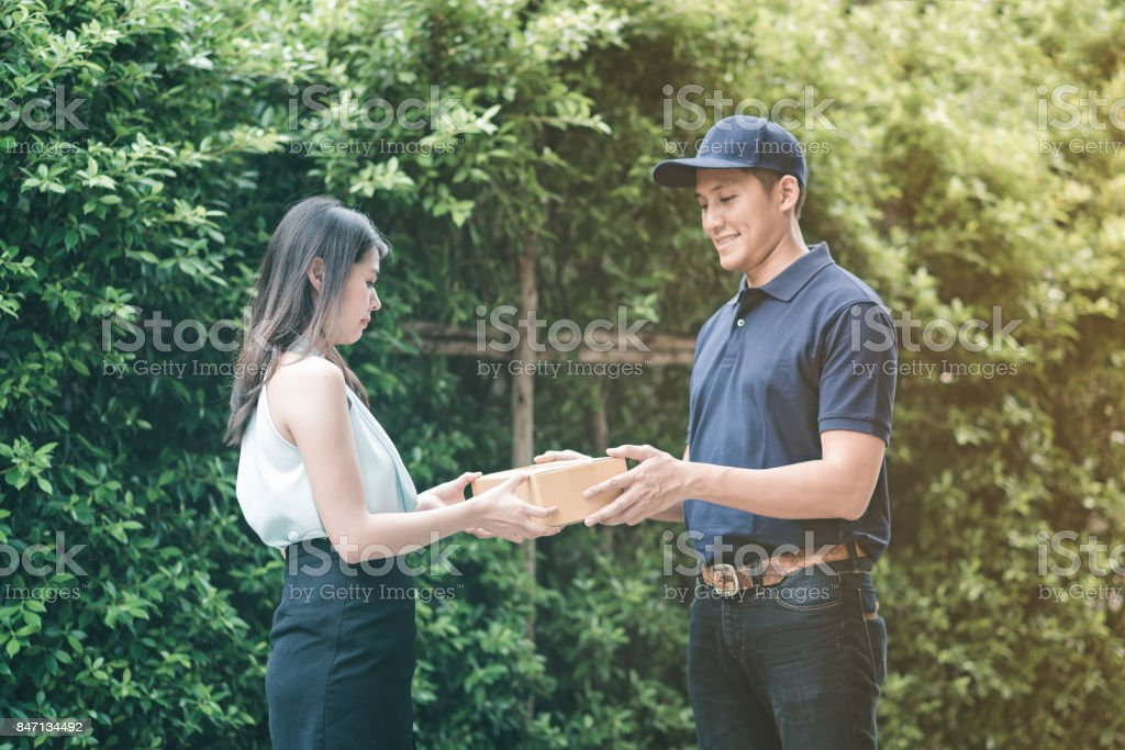 Handsome young asian delivery man smiling and giving a cardboard box to his customer stock photo