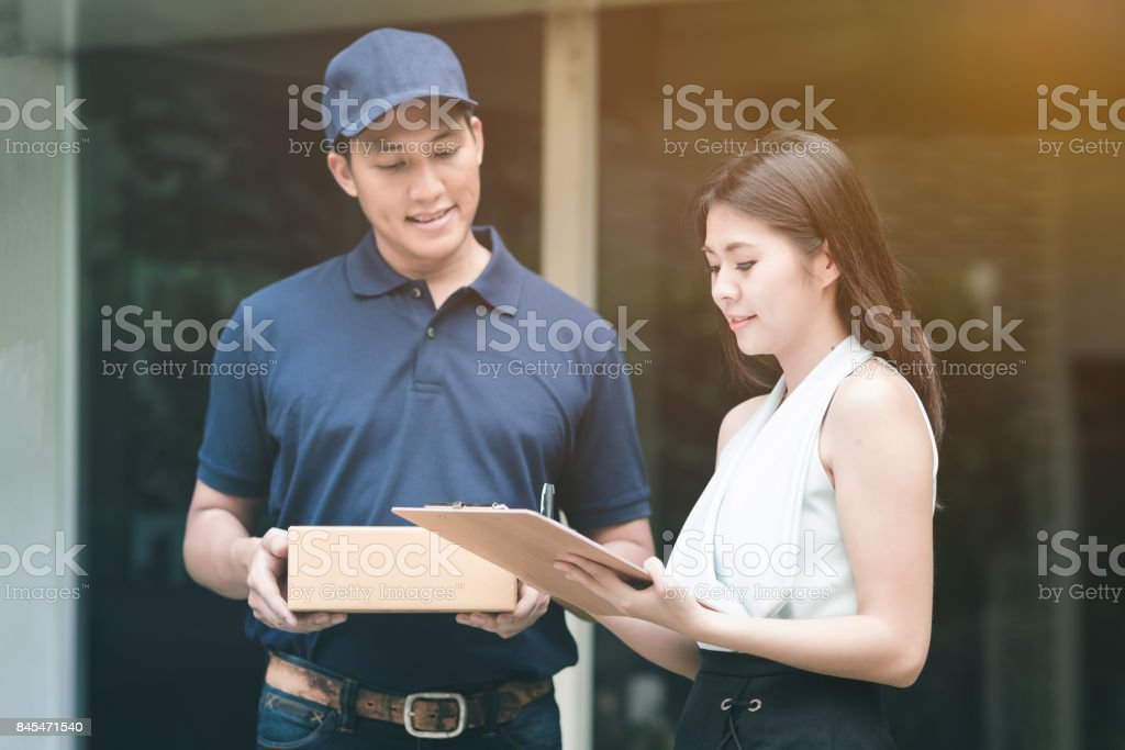 Handsome young asian delivery man smiling and holding a cardboard box stock photo