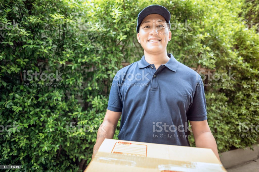 Handsome young asian delivery man smiling while holding a cardboard box delivery to his customer. stock photo