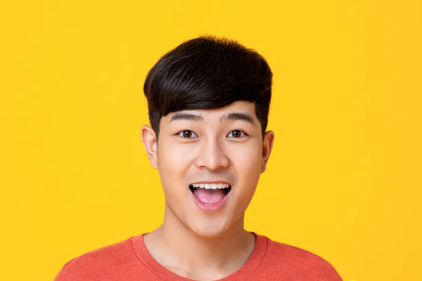 Handsome young Asian man face smiling with mouth open Studio portrait of  handsome young Asian man face smiling with mouth open isolated on colorful yellow background mouth open stock pictures, royalty-free photos & images