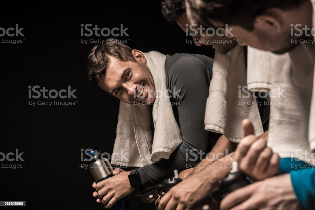Handsome young athletes resting at gym locker room stock photo