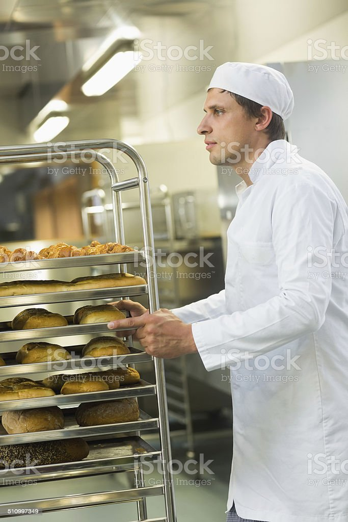 Handsome young baker pushing a trolley stock photo