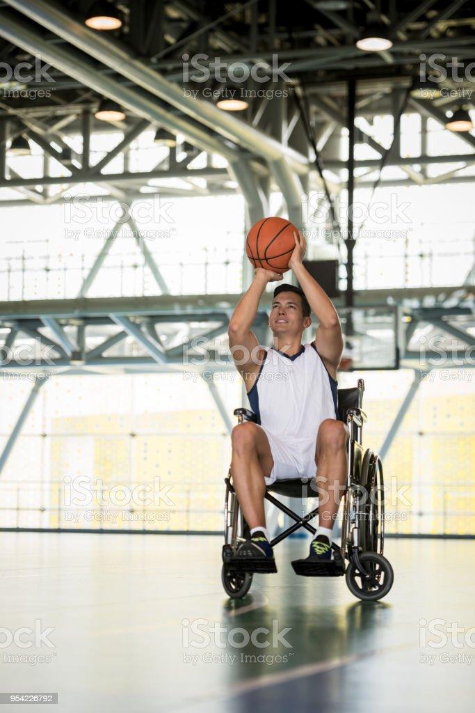 ボールを投げる準備ができて車椅子でハンサムな若いバスケット ボール選手 ストックフォト