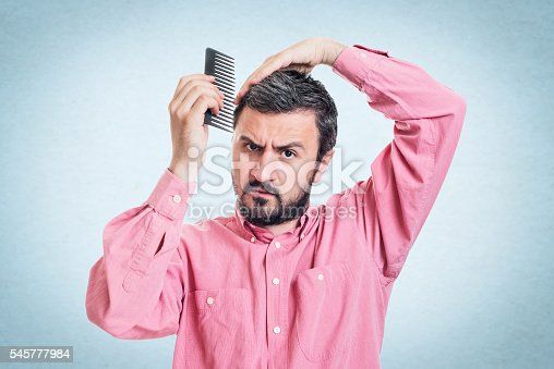 1134770826 istock photo Handsome young beard man combing his hair 545777984