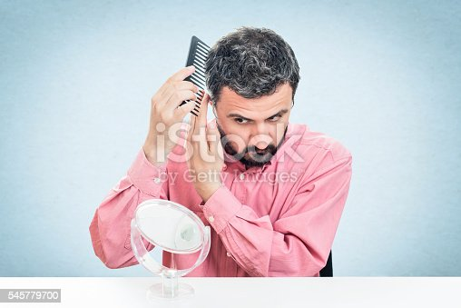 1134770826 istock photo Handsome young beard man combing his hair 545779700