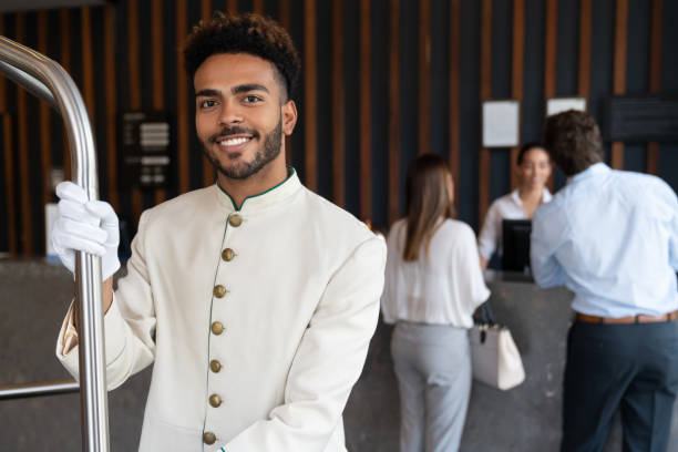 Handsome young black bellhop looking at camera smiling while holding luggage cart stock photo