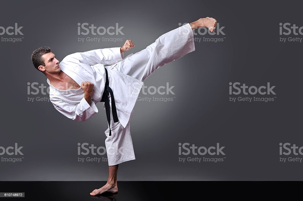 Handsome young black belt male karate doing kick ストックフォト