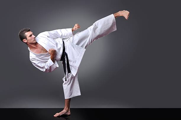 handsome young black belt male karate doing kick - karate stock-fotos und bilder