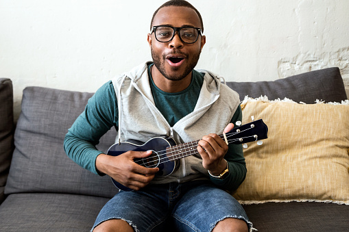 istock Handsome young black man playing the guitar at home. 544994240