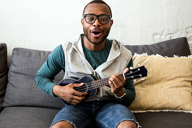 handsome young black man playing the guitar at home. - ukulele songs stock-fotos und bilder