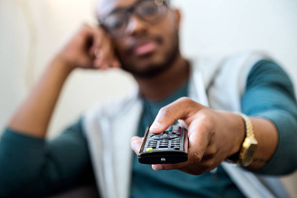 Handsome young black man watching tv at home. stock photo