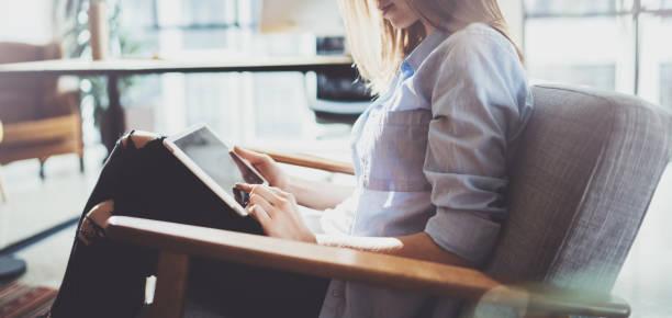Hübsche junge Blondine Brille und mit elektronischen Touch Tablet-Computer auf sonnigen Arbeitsplatz. Horizontale. Der Hintergrund jedoch unscharf. – Foto