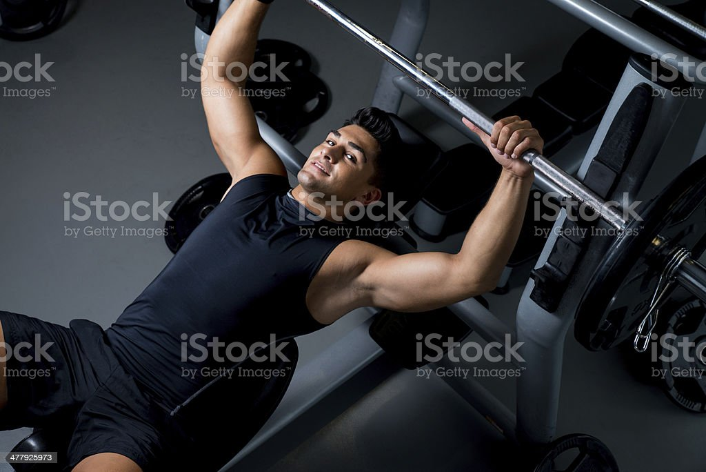 Handsome young bodybuilder smilingly prepares for exercise royalty-free stock photo