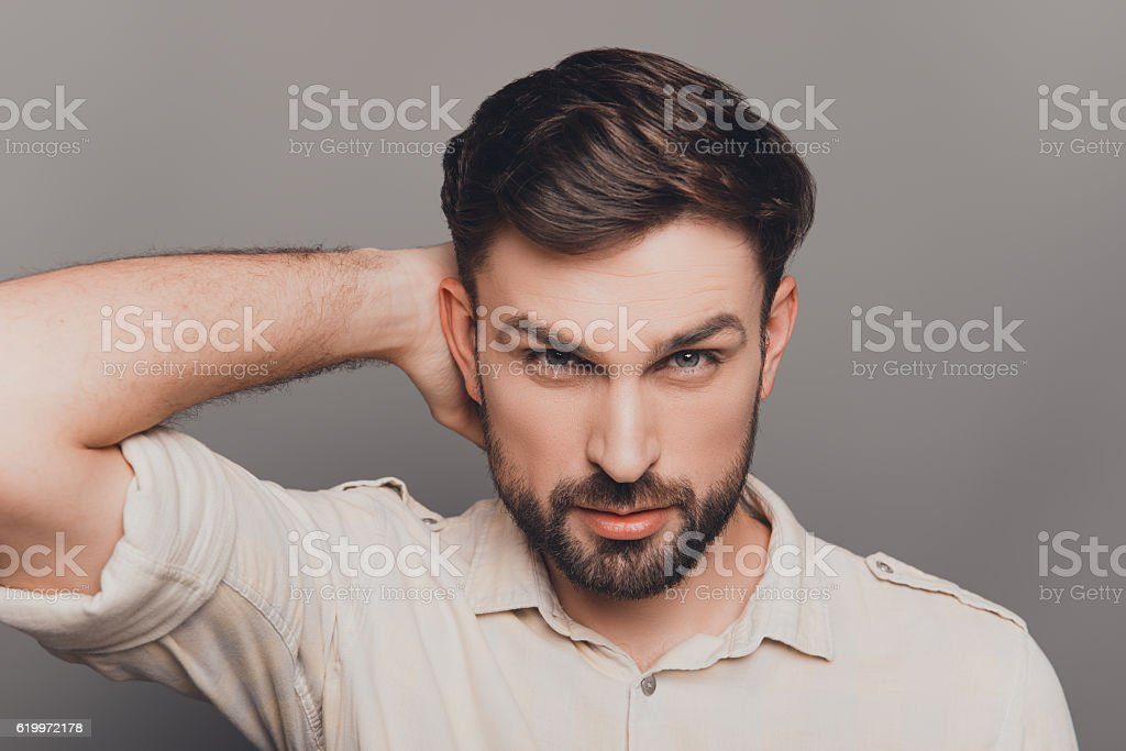 Handsome young brunet touching head and combining hair stock photo