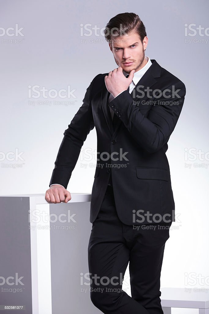 Handsome young business man leaning on a white table stock photo