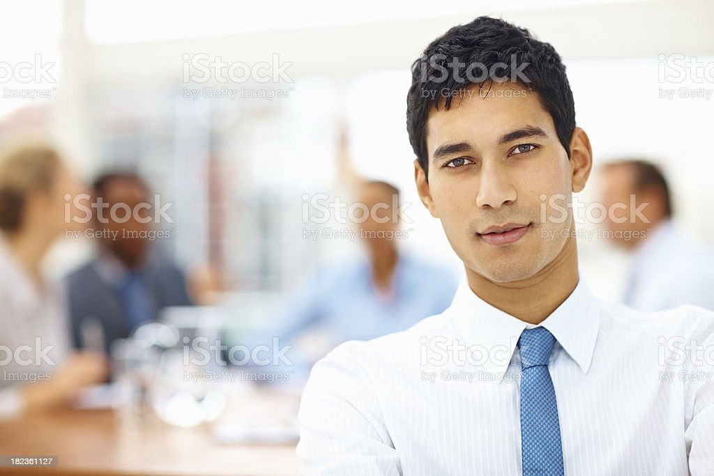 Handsome young business man with colleagues at the back royalty-free stock photo