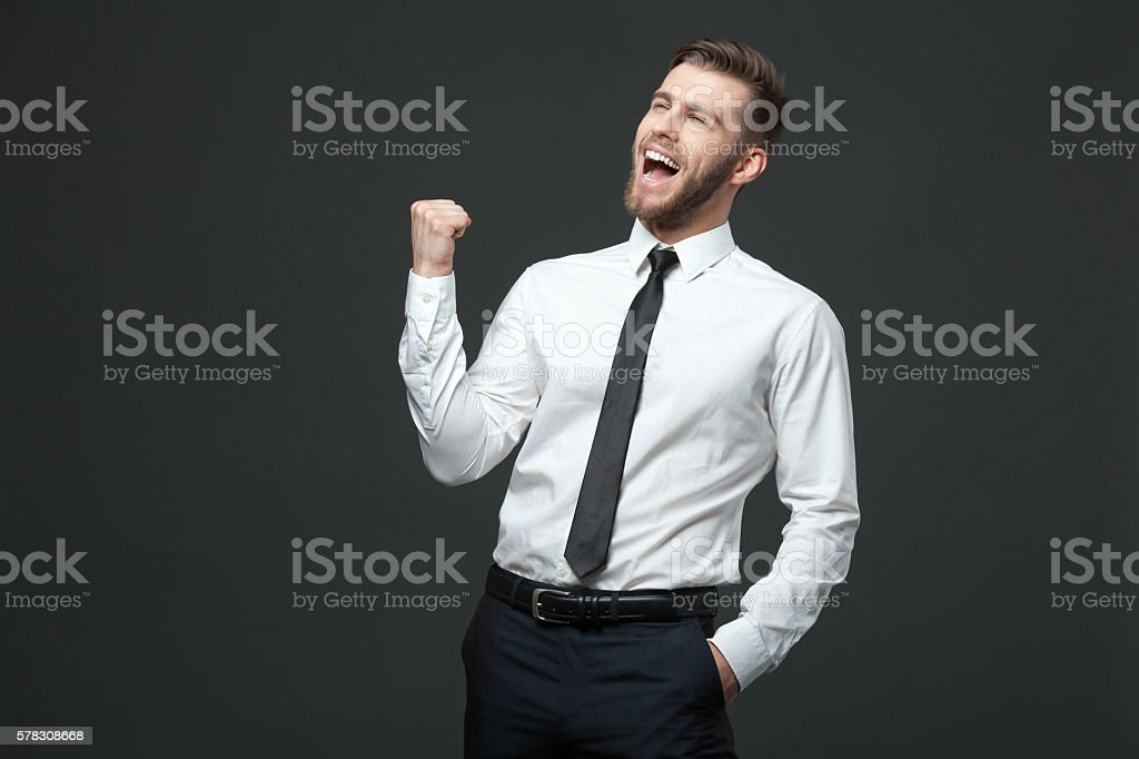 Handsome young businessman celebrating his success. stock photo