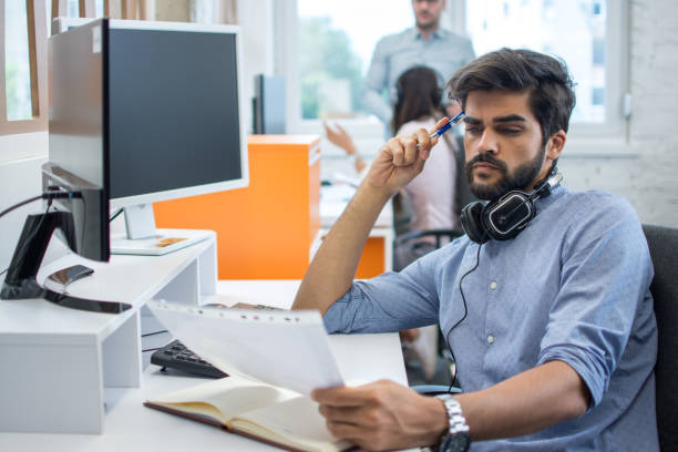 Handsome junger Geschäftsmann, der Papiere und Dokumente an seinem Arbeitsplatz im Büro überprüft – Foto
