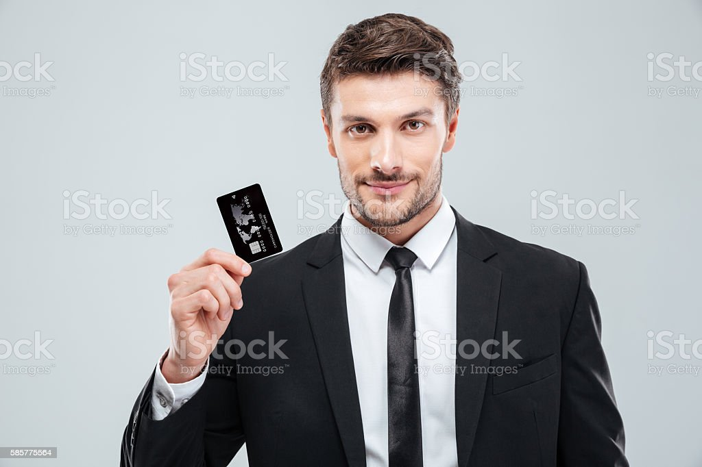 Handsome young businessman holding credit card stock photo