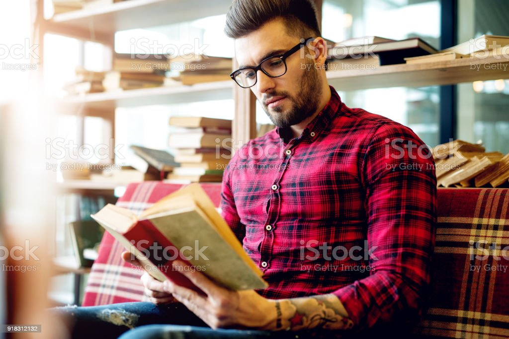 Handsome young businessman in casual clothes and eyeglasses reading a book. stock photo