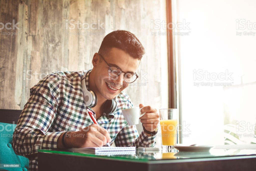 Handsome young businessman is using a tablet and smiling, sitting at bar counter in a modern urban cafe stock photo
