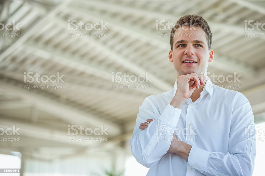 Handsome young businessman looking away in office stock photo