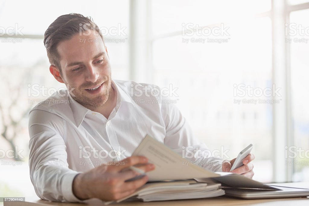 Handsome young businessman reading brochure at office desk stock photo