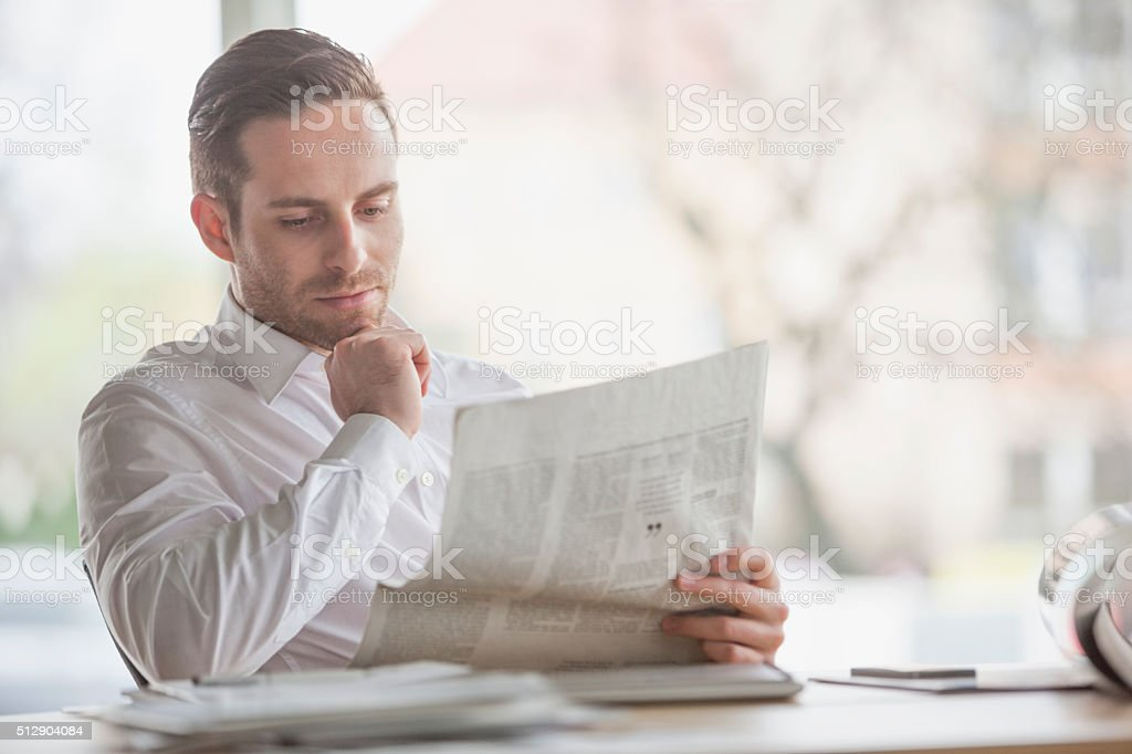 Handsome young businessman reading newspaper at office desk stock photo