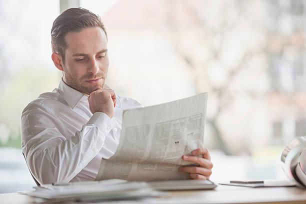 Attraktive junge Geschäftsmann liest Zeitung im Büro-Schreibtisch – Foto