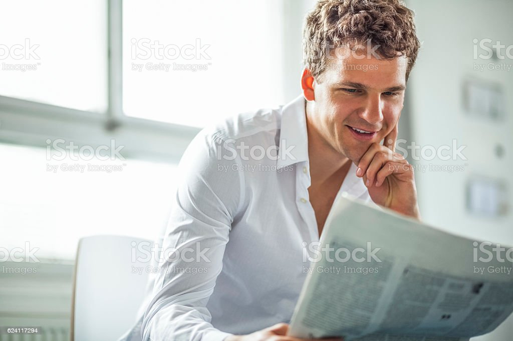 Handsome young businessman reading newspaper in office stock photo