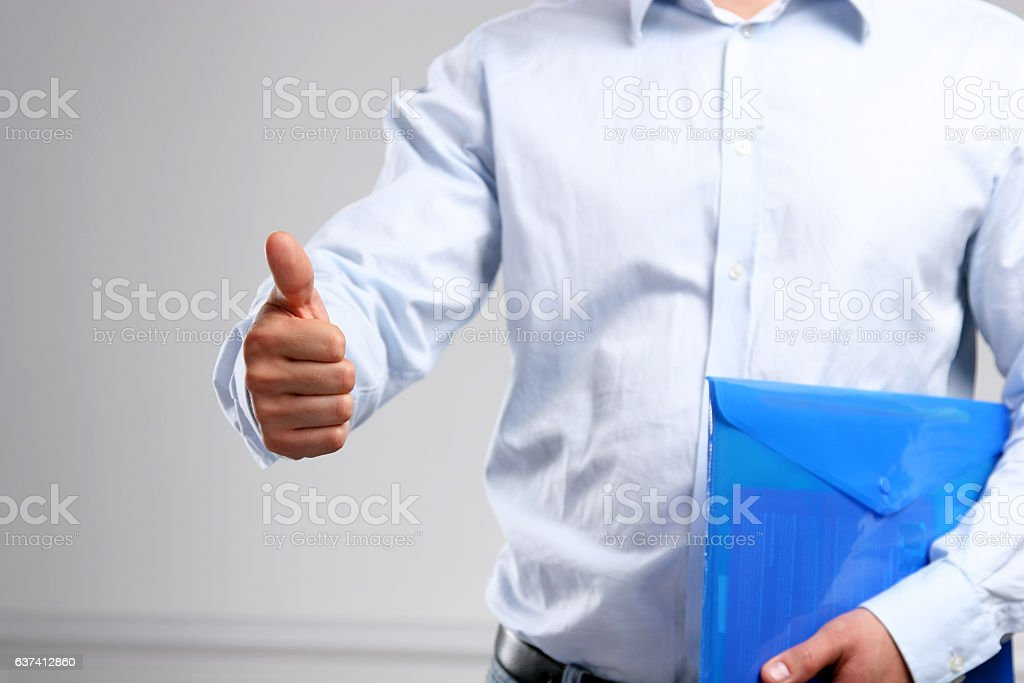 Handsome young businessman showing ok standing with folder stock photo