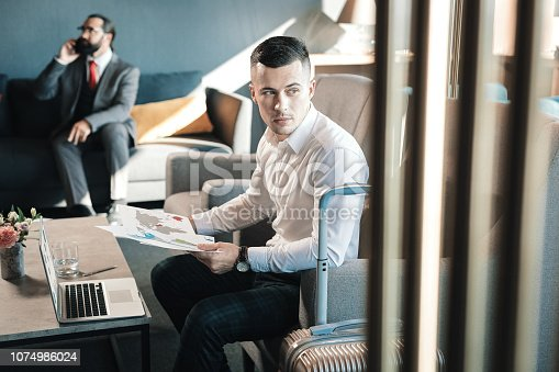 istock Handsome young businessman sitting in armchair working hard 1074986024