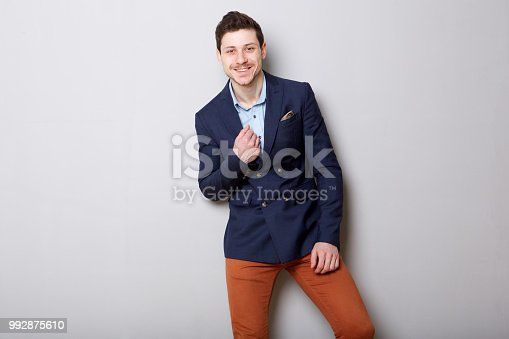 Portrait of handsome young businessman smiling against gray background