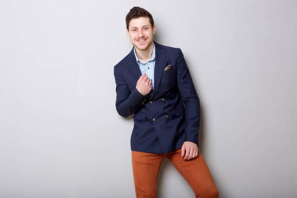knappe jonge zakenman glimlachend tegen de grijze achtergrond - men blazer stockfoto's en -beelden