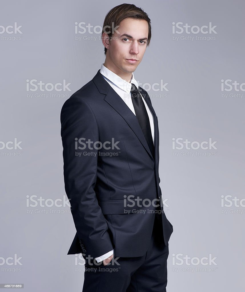 Handsome young businessman standing against gray background royalty-free stock photo
