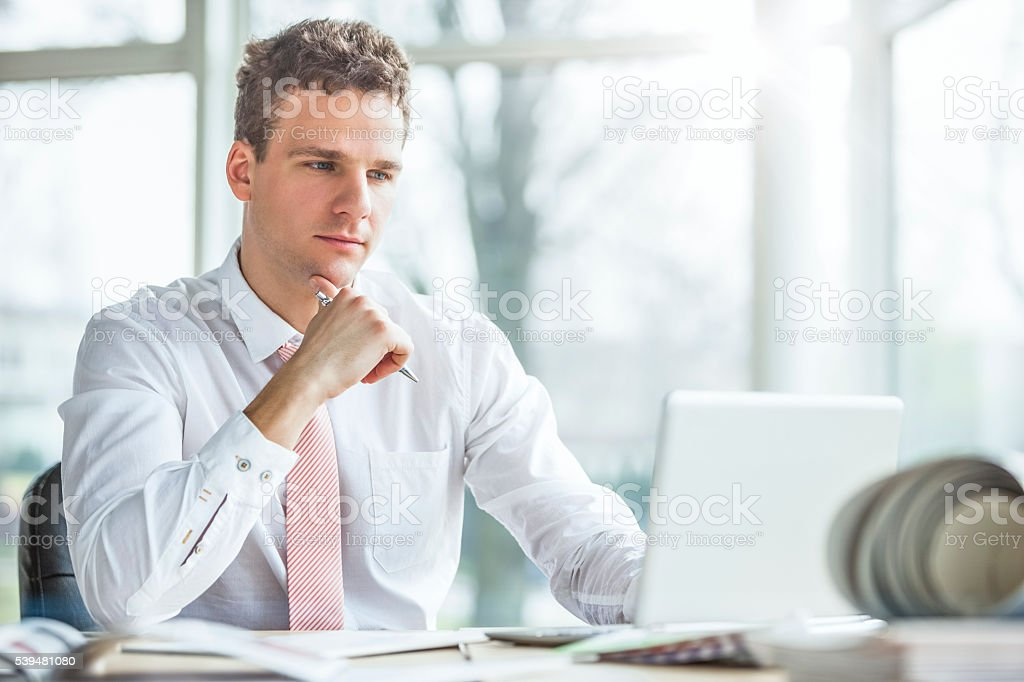 Handsome young businessman using laptop at office desk stock photo