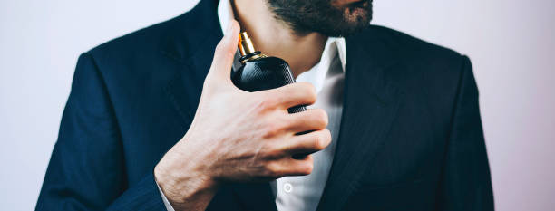 Handsome young businessman using perfume stock photo