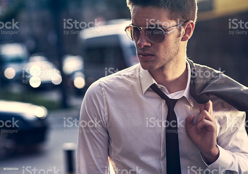 handsome young businessman walking on the way home stock photo