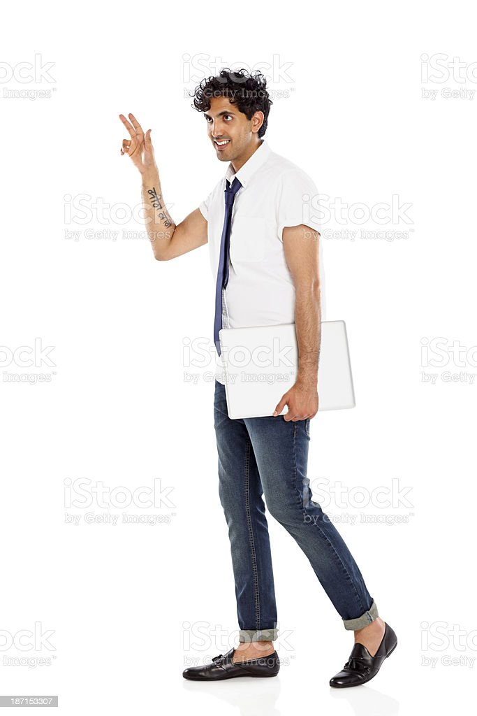 Handsome young businessman with a laptop waving away royalty-free stock photo