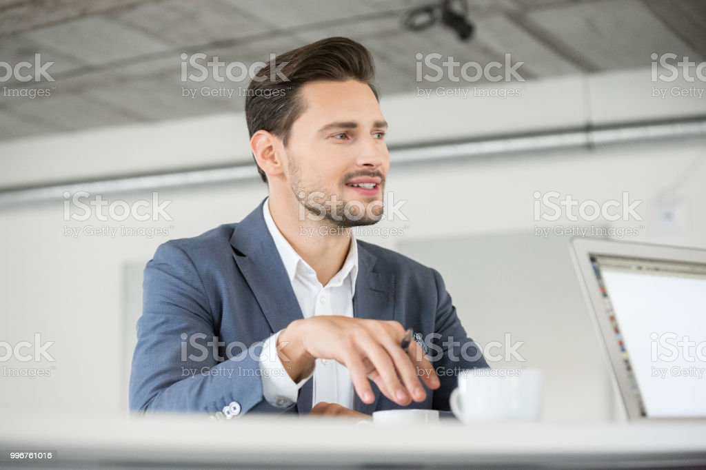Handsome young businessman working in office Handsome young businessman talking with colleague sitting on the other side of the table. Male executive working in office. 25-29 Years Stock Photo