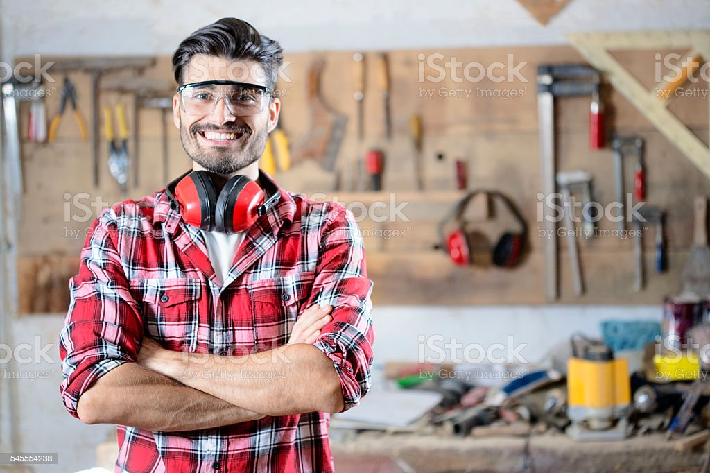 Handsome young carpenter posing in his workshop stock photo
