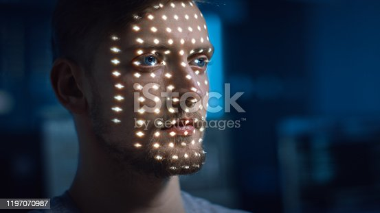 istock Handsome Young Caucasian Man is Identified by Biometric Facial Recognition Scanning Process. Futuristic Concept: Projector Identifies Individual by Illuminating Face by Dots and Scanning with Laser 1197070987