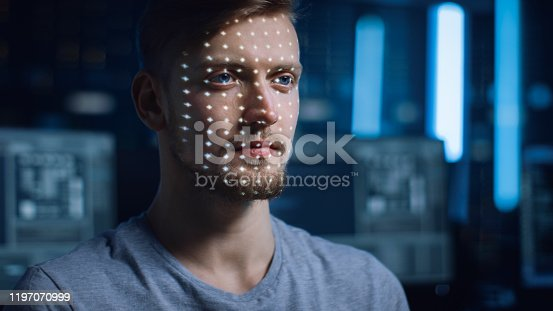istock Handsome Young Caucasian Man is Identified by Biometric Facial Recognition Scanning Process. Futuristic Concept: Projector Identifies Individual by Illuminating Face by Dots and Scanning with Laser 1197070999