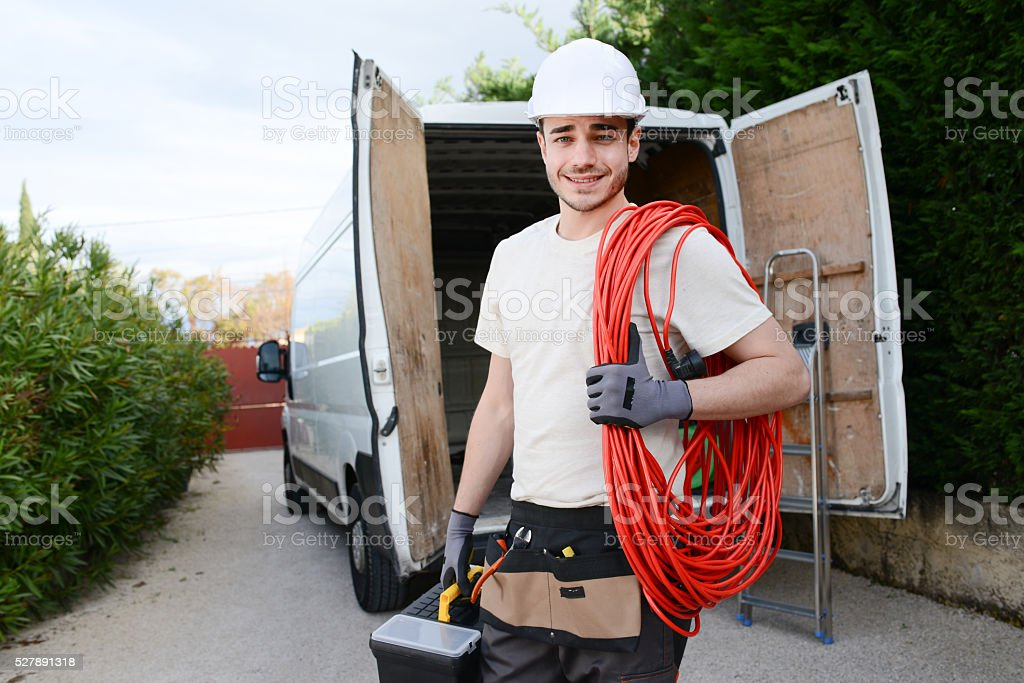 handsome young construction worker with commercial van on background stock photo