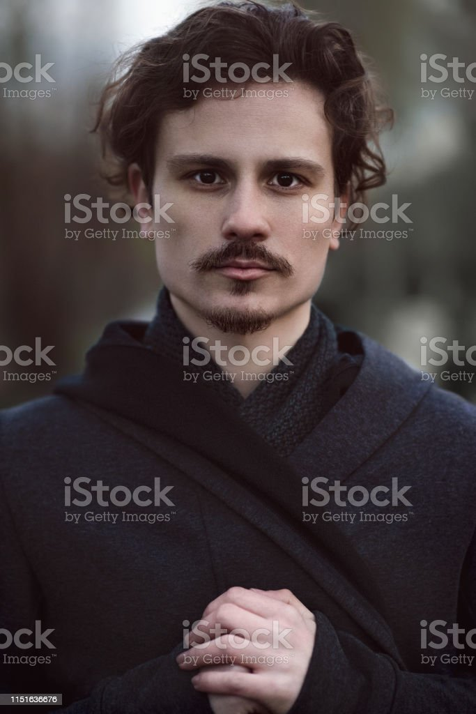Handsome young curly man prays with all one\'s soul. Invocation to the...