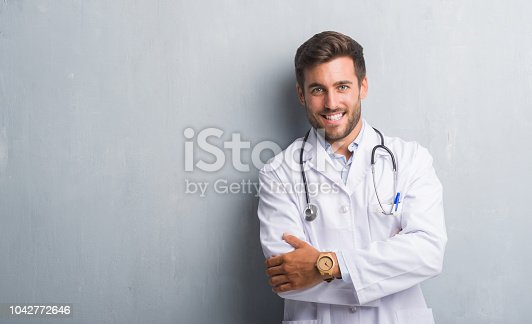 Handsome young doctor man over grey grunge wall happy face smiling with crossed arms looking at the camera. Positive person.
