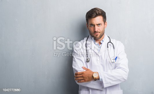 Handsome young doctor man over grey grunge wall skeptic and nervous, disapproving expression on face with crossed arms. Negative person.