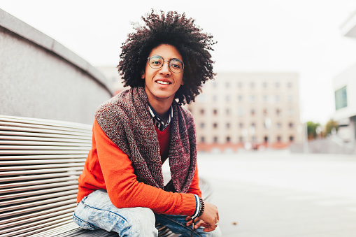 istock A handsome young Egyptian curly guy sitting on a bench dressed in a bright orange sweater and jeans. Happy people. The student walks in the break between the lessons. 1065218592