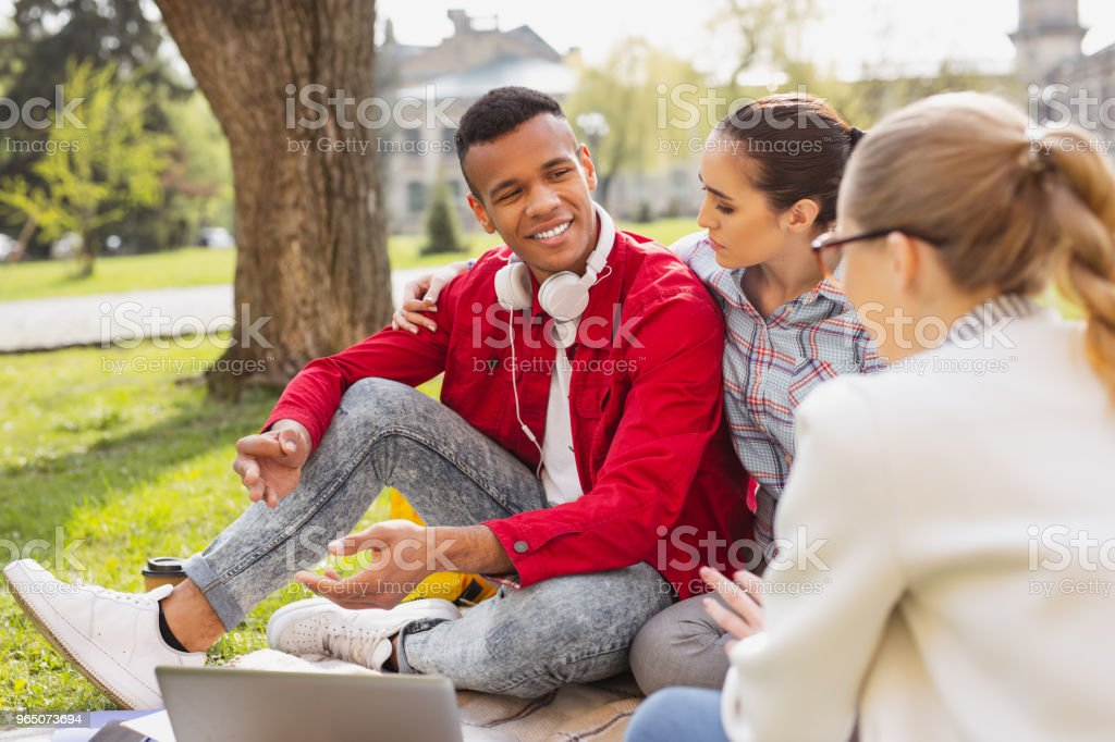 Handsome young fellow feeling good sitting near his girlfriend royalty-free stock photo